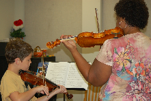 Community Music and Dance Academy teacher Angela Diaw gives this young violinist a lesson.