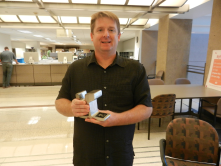 Sean McClue with his piece of the light rail track he redeemed at the Rewards Store.