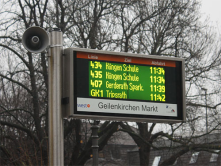 An electronic display shows the zone number, the destination and the departure time for each bus at a bus stop in Aachen, Germany.