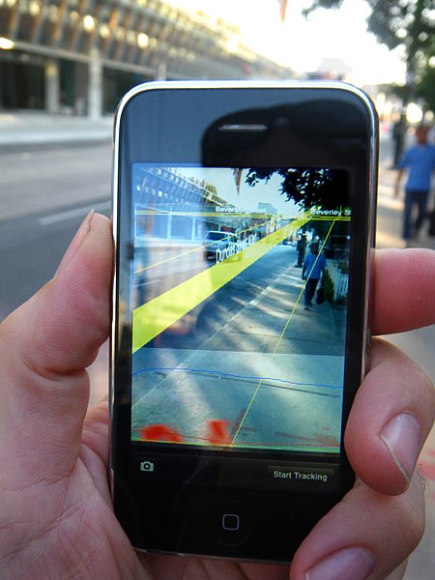 a cell phone with a camera capturing the view of the street and overlaying the digital street. augmented Reality