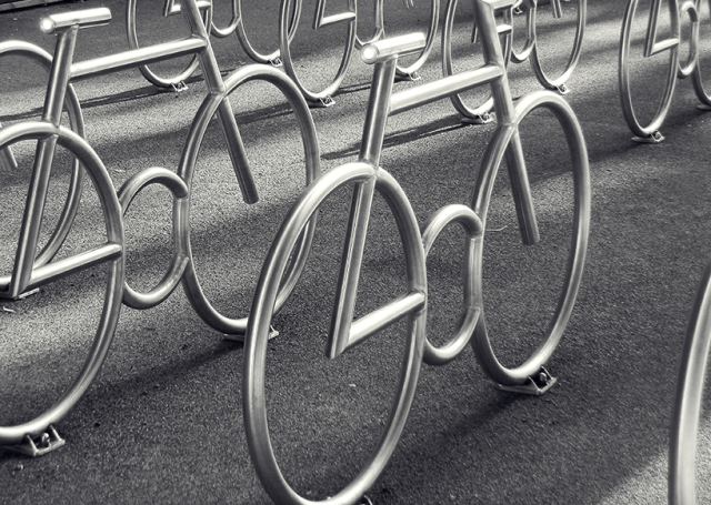 Bicycle stands with a bicycle theme by MAD arkitekter. The stylized bicycle structures of stainless steel provide safe bicycle parking.
