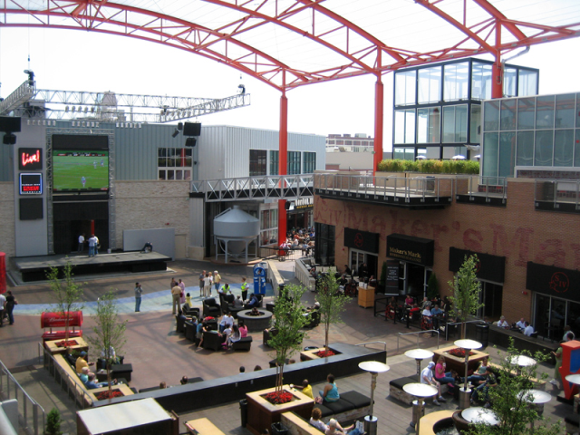 An entertainment district that features restaurants with outdoor seating, a stage, and covered central seating area.