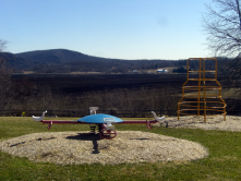 This photo shows the playground of the now-closed Pine Island Elementary School with a black dirt farm in the background.